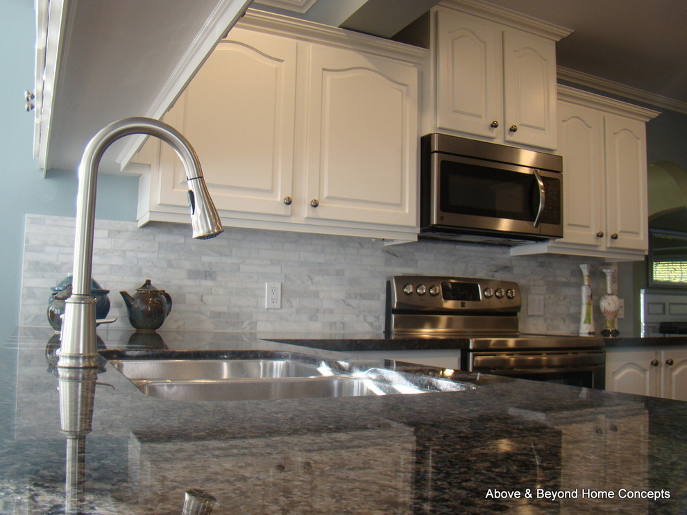 Example of a transitional u-shaped eat-in kitchen design in Vancouver with an undermount sink, raised-panel cabinets, white cabinets, granite countertops, white backsplash, stone tile backsplash and stainless steel appliances
