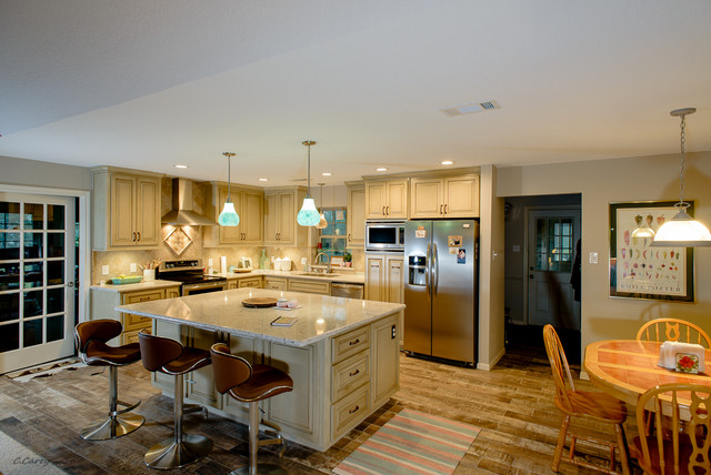 Eat-in kitchen - mid-sized l-shaped porcelain floor eat-in kitchen idea in Houston with an undermount sink, raised-panel cabinets, distressed cabinets, quartz countertops, beige backsplash, stone tile backsplash, stainless steel appliances and an island