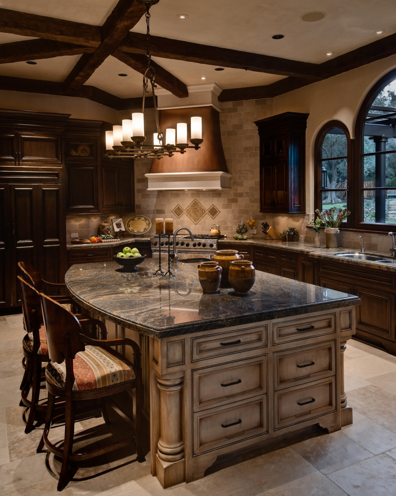 Inspiration for a large mediterranean l-shaped travertine floor and beige floor open concept kitchen remodel in San Francisco with an undermount sink, recessed-panel cabinets, beige cabinets, marble countertops, beige backsplash, travertine backsplash, stainless steel appliances and an island