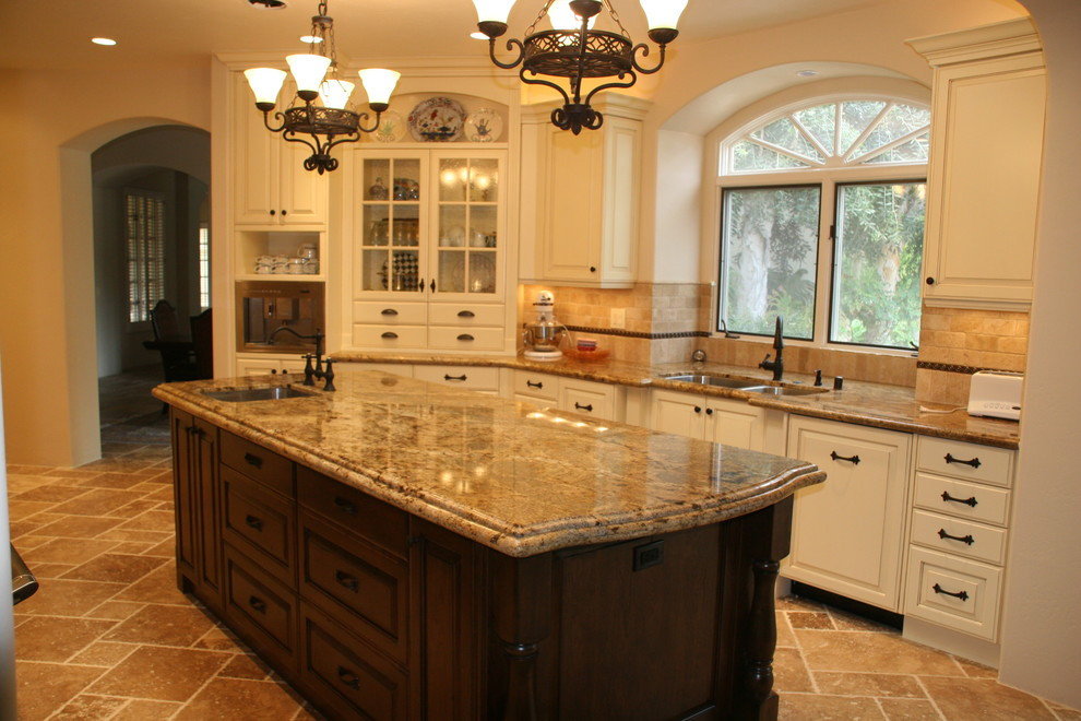 Example of a mid-sized classic l-shaped limestone floor and beige floor open concept kitchen design in San Diego with a double-bowl sink, raised-panel cabinets, white cabinets, granite countertops, beige backsplash, ceramic backsplash, paneled appliances, an island and beige countertops