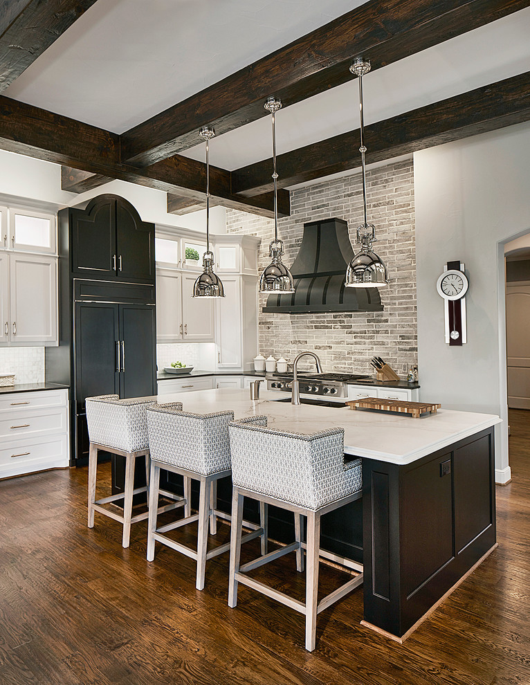 Kitchen - transitional l-shaped dark wood floor kitchen idea in Dallas with shaker cabinets, white cabinets, gray backsplash, an island and paneled appliances
