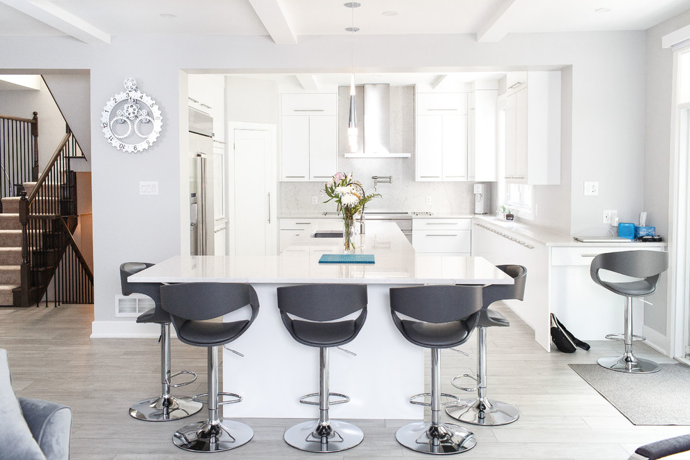 Example of a mid-sized trendy gray floor open concept kitchen design in Ottawa with an undermount sink, flat-panel cabinets, white cabinets, quartz countertops, stainless steel appliances, an island, white countertops, gray backsplash and stone slab backsplash