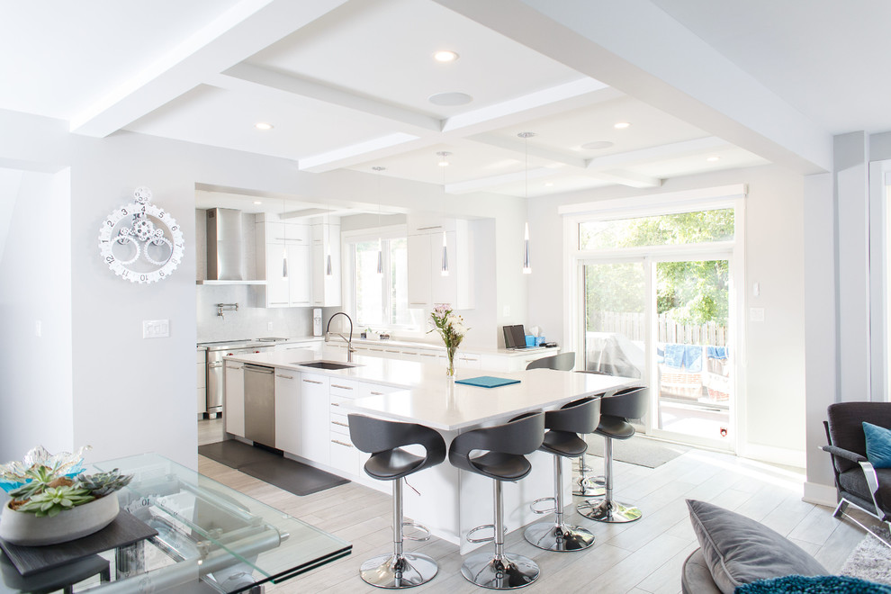 Mid-sized trendy u-shaped ceramic tile and gray floor kitchen photo in Ottawa with an undermount sink, flat-panel cabinets, white cabinets, quartz countertops, white backsplash, stainless steel appliances, an island and white countertops