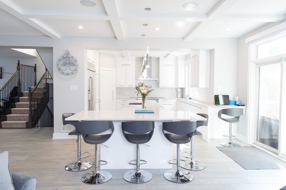 Example of a mid-sized trendy u-shaped ceramic tile and gray floor kitchen design in Ottawa with an undermount sink, flat-panel cabinets, white cabinets, quartz countertops, white backsplash, stainless steel appliances, an island and white countertops