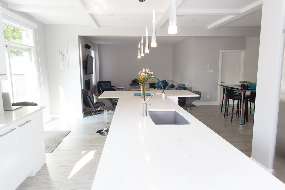 Inspiration for a mid-sized contemporary u-shaped ceramic tile and gray floor kitchen remodel in Ottawa with an undermount sink, flat-panel cabinets, white cabinets, quartz countertops, white backsplash, stainless steel appliances, an island and white countertops