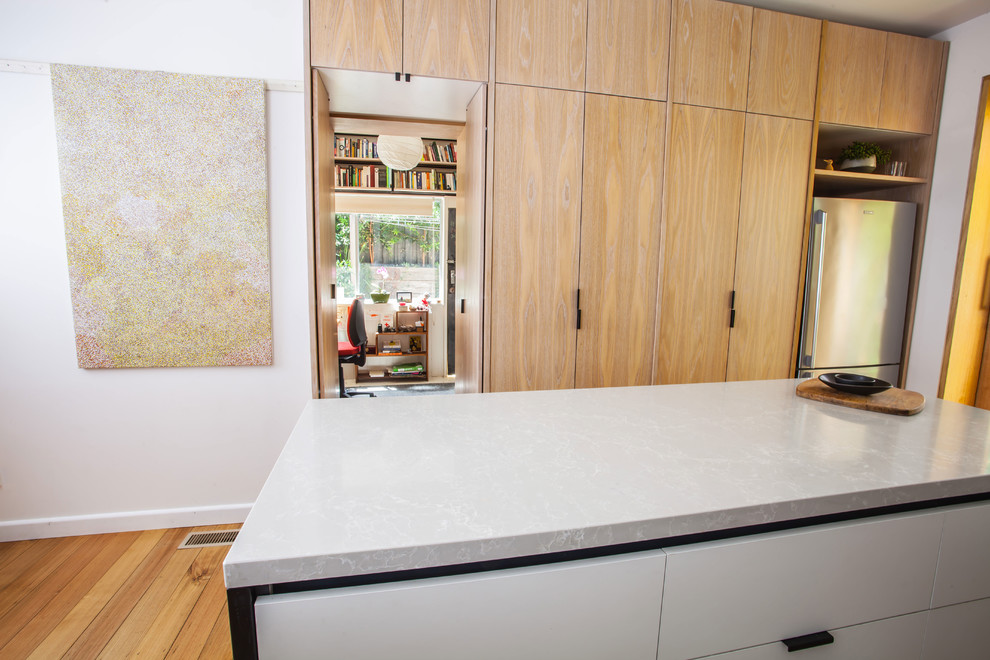 Design ideas for a mid-sized contemporary u-shaped open plan kitchen in Melbourne with a double-bowl sink, flat-panel cabinets, white cabinets, stainless steel benchtops, green splashback, ceramic splashback, stainless steel appliances, medium hardwood floors and an island.