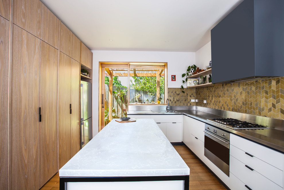 Photo of a mid-sized contemporary u-shaped open plan kitchen in Melbourne with a double-bowl sink, flat-panel cabinets, white cabinets, stainless steel benchtops, green splashback, ceramic splashback, stainless steel appliances, medium hardwood floors and an island.