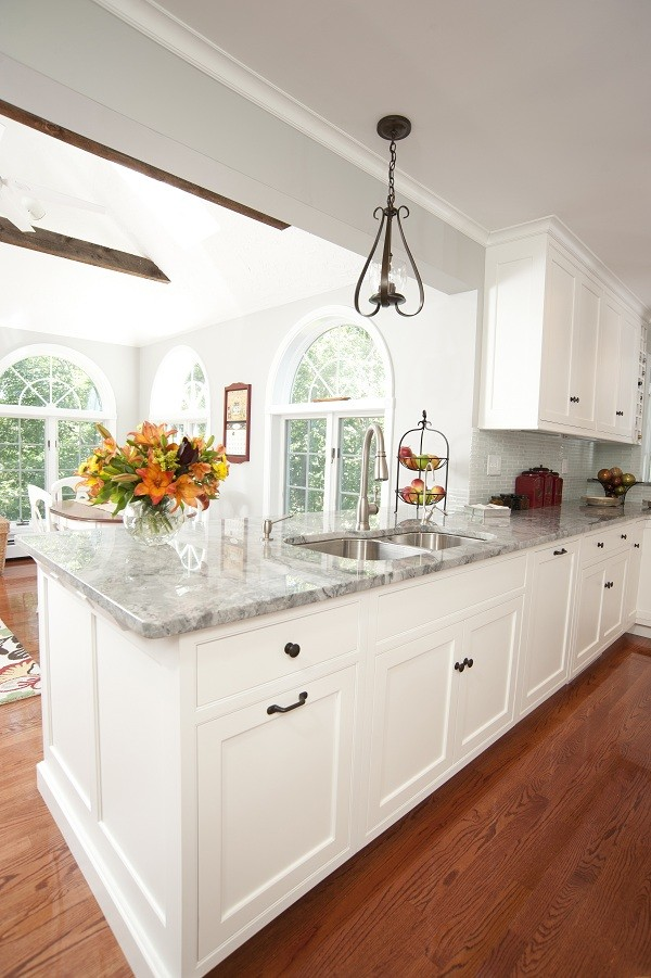 Inspiration for a large timeless medium tone wood floor open concept kitchen remodel in Boston with a double-bowl sink, recessed-panel cabinets, white cabinets, granite countertops, paneled appliances and an island