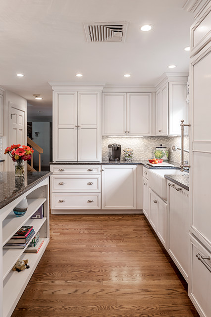 Elegant kitchen photo in Boston with a farmhouse sink, recessed-panel cabinets, white cabinets, gray backsplash and paneled appliances