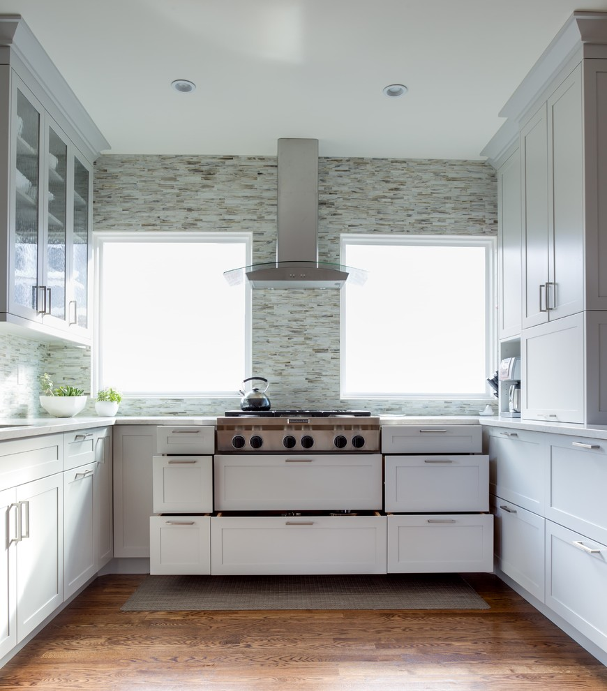 Example of a mid-sized trendy u-shaped enclosed kitchen design in Denver with shaker cabinets, white cabinets and a peninsula
