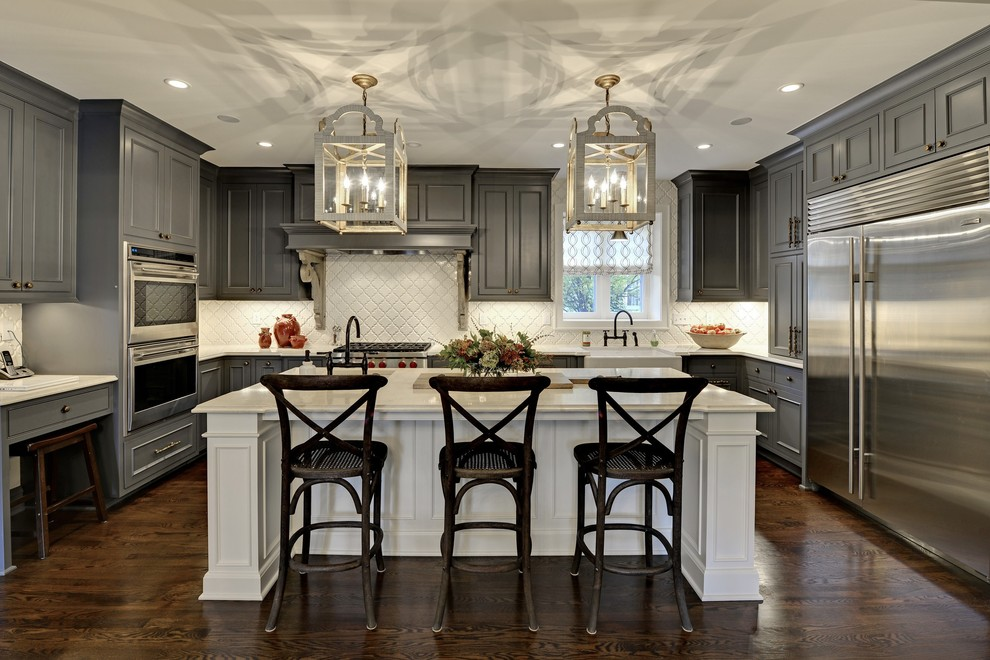 Large transitional u-shaped dark wood floor and brown floor eat-in kitchen photo in Minneapolis with gray cabinets, white backsplash, stainless steel appliances, an island, raised-panel cabinets, a farmhouse sink, solid surface countertops, white countertops and ceramic backsplash