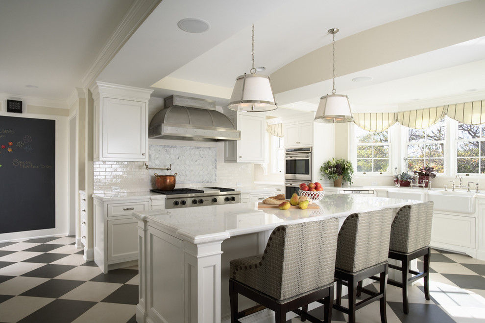 Example of a large classic u-shaped multicolored floor enclosed kitchen design in Minneapolis with stainless steel appliances, a farmhouse sink, recessed-panel cabinets, white cabinets, marble countertops, white backsplash, stone tile backsplash and an island