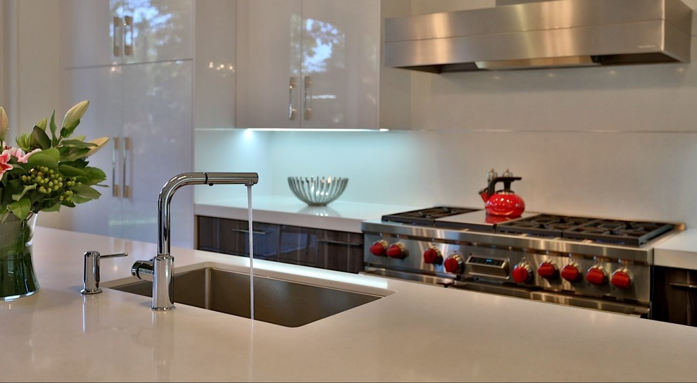 Inspiration for a mid-sized contemporary l-shaped dark wood floor eat-in kitchen remodel in Toronto with an undermount sink, flat-panel cabinets, white cabinets, white backsplash, stainless steel appliances and an island