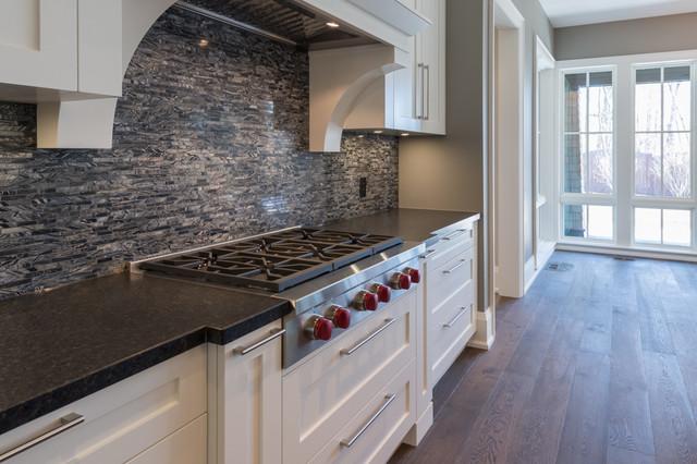 Enclosed kitchen - large transitional l-shaped medium tone wood floor enclosed kitchen idea in Toronto with a single-bowl sink, shaker cabinets, white cabinets, granite countertops, black backsplash, mosaic tile backsplash, white appliances and an island