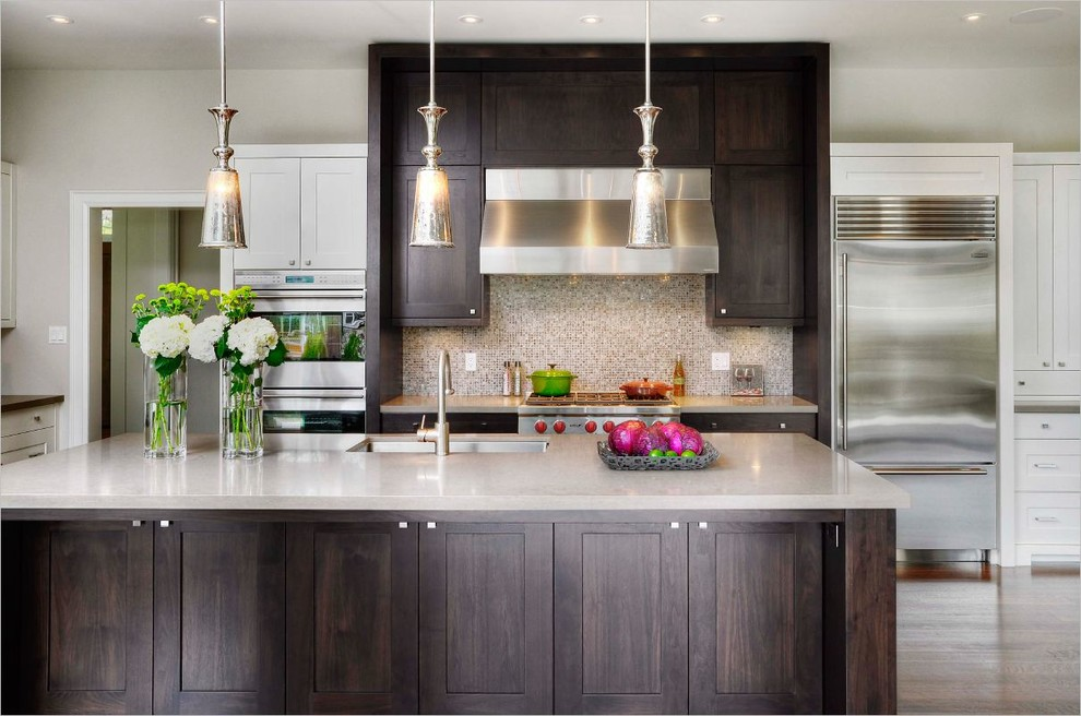 Example of a mid-sized transitional l-shaped light wood floor eat-in kitchen design in Toronto with an undermount sink, shaker cabinets, granite countertops, metallic backsplash, mosaic tile backsplash, stainless steel appliances, an island and white cabinets