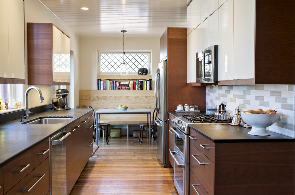 Trendy galley enclosed kitchen photo in Louisville with an undermount sink, flat-panel cabinets, gray backsplash, ceramic backsplash, stainless steel appliances and medium tone wood cabinets