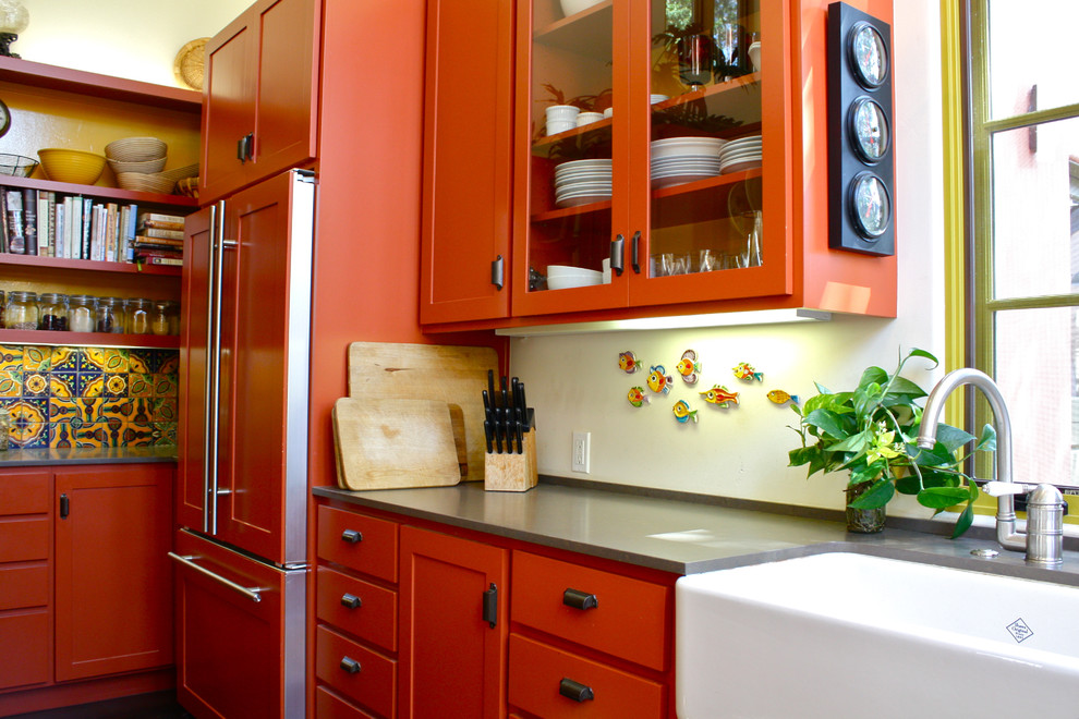 Kitchen - southwestern kitchen idea in Santa Barbara with glass-front cabinets, a farmhouse sink, orange cabinets and paneled appliances