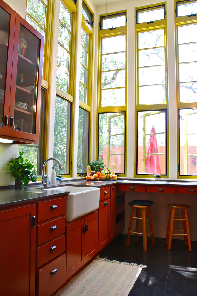 Southwest kitchen photo in Santa Barbara with glass-front cabinets, a farmhouse sink and orange cabinets