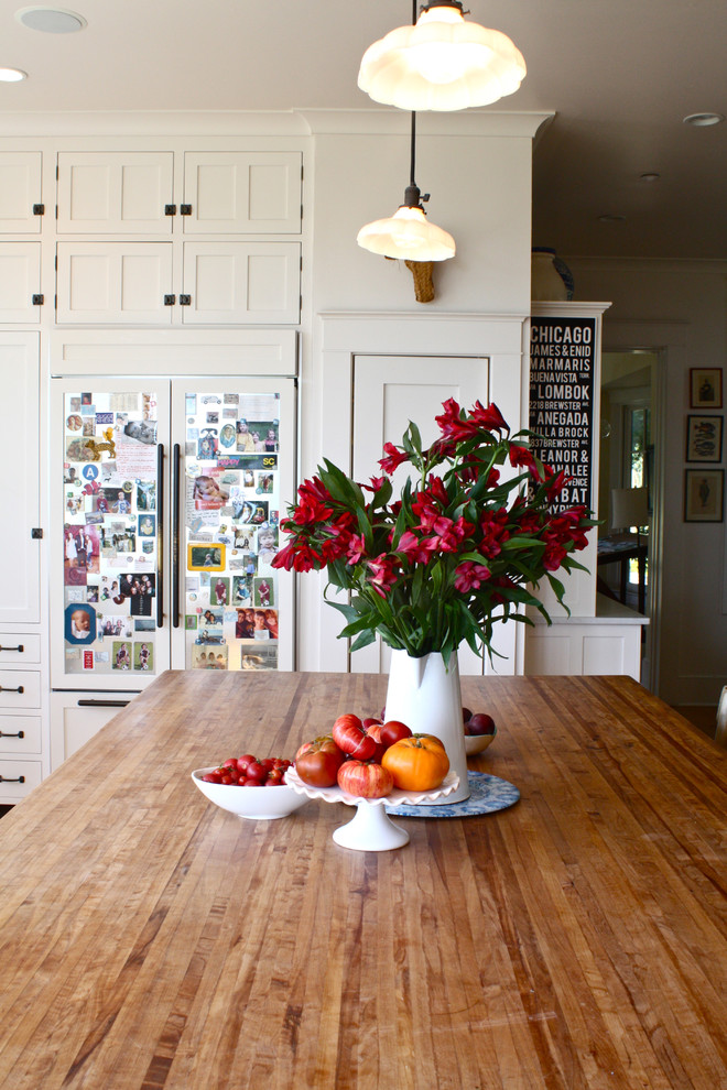 Example of a classic kitchen design in San Francisco with wood countertops, white cabinets and paneled appliances