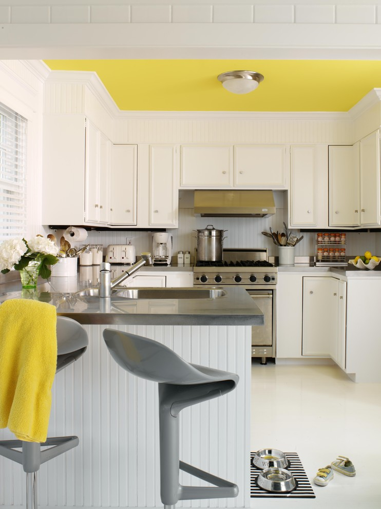 Inspiration for a mid-sized contemporary u-shaped laminate floor and white floor eat-in kitchen remodel in New York with recessed-panel cabinets, white cabinets, stainless steel appliances, a double-bowl sink, solid surface countertops, white backsplash, a peninsula and gray countertops