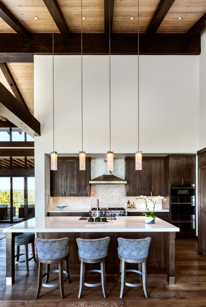 Example of a mid-sized mountain style l-shaped dark wood floor and brown floor kitchen design in Phoenix with a farmhouse sink, shaker cabinets, dark wood cabinets, white backsplash, mosaic tile backsplash, stainless steel appliances, an island and white countertops