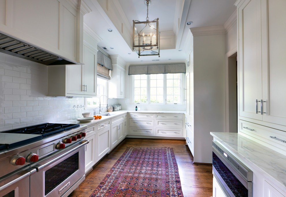 Enclosed kitchen - transitional u-shaped enclosed kitchen idea in Charlotte with stainless steel appliances, an undermount sink, recessed-panel cabinets, white cabinets, white backsplash and subway tile backsplash