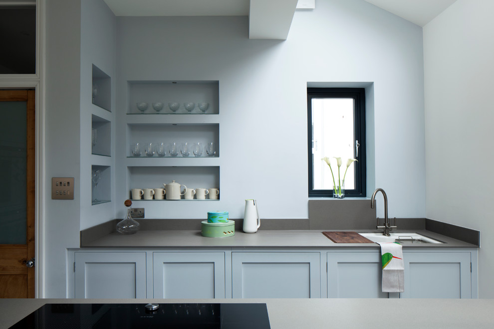 Trendy galley kitchen photo in London with an undermount sink, shaker cabinets and blue cabinets