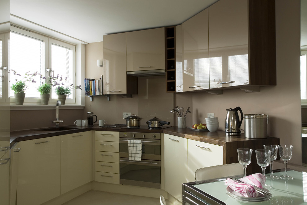 Eclectic eat-in kitchen photo in London with flat-panel cabinets, beige cabinets, brown backsplash and stainless steel appliances