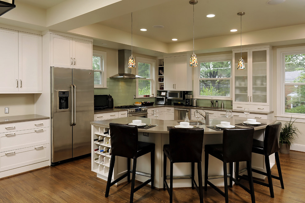 Example of a trendy l-shaped kitchen design in DC Metro with glass tile backsplash, stainless steel appliances, quartz countertops, green backsplash, recessed-panel cabinets and white cabinets
