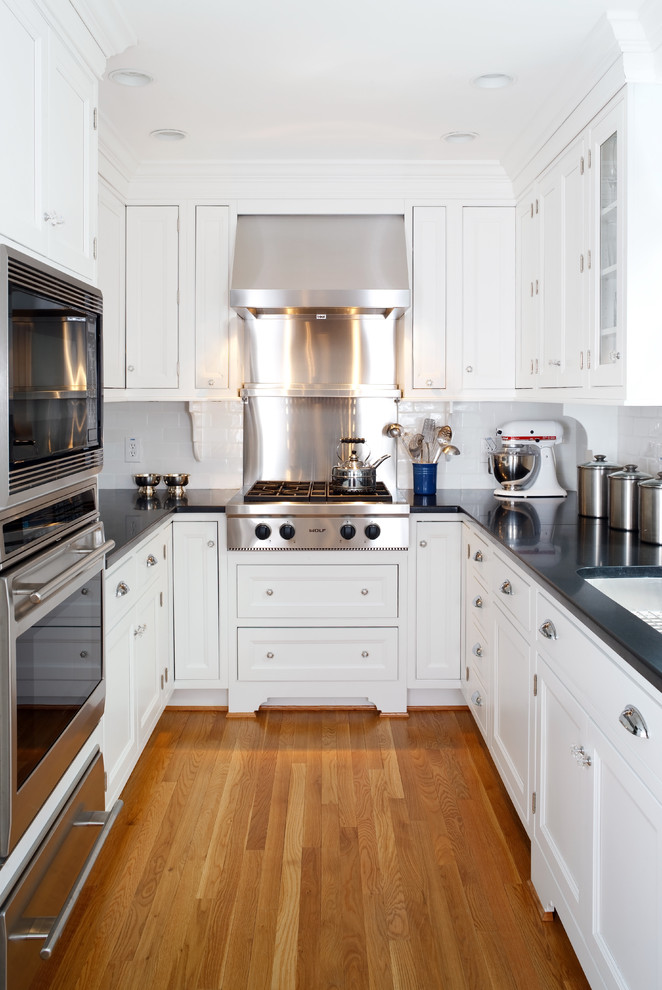 Example of a classic enclosed kitchen design in DC Metro with stainless steel appliances, recessed-panel cabinets, white cabinets, white backsplash and subway tile backsplash