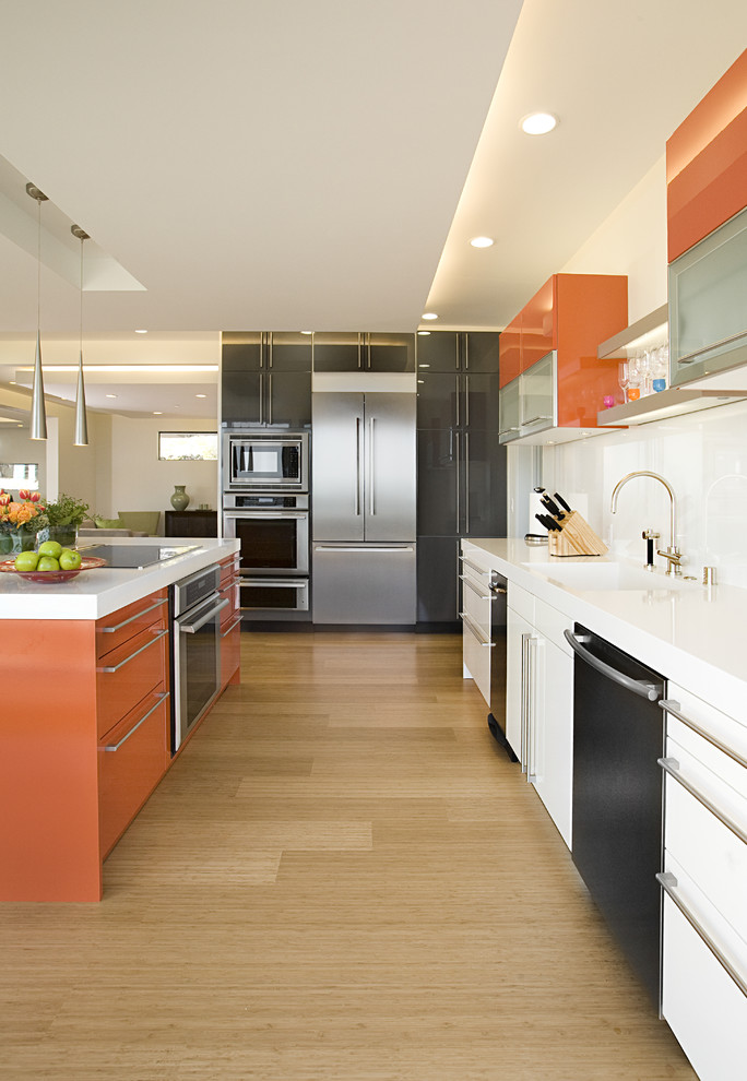 Mid-sized trendy galley bamboo floor and beige floor eat-in kitchen photo in San Francisco with stainless steel appliances, an integrated sink, flat-panel cabinets, orange cabinets and white backsplash