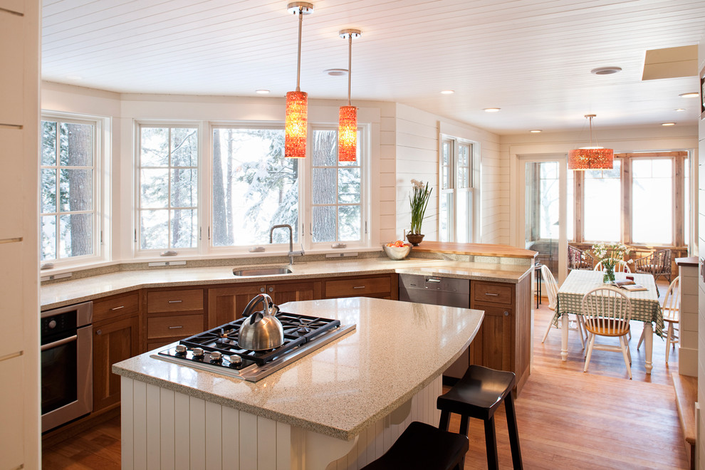 Elegant u-shaped eat-in kitchen photo in Portland Maine with recycled glass countertops, an undermount sink, shaker cabinets, medium tone wood cabinets and stainless steel appliances