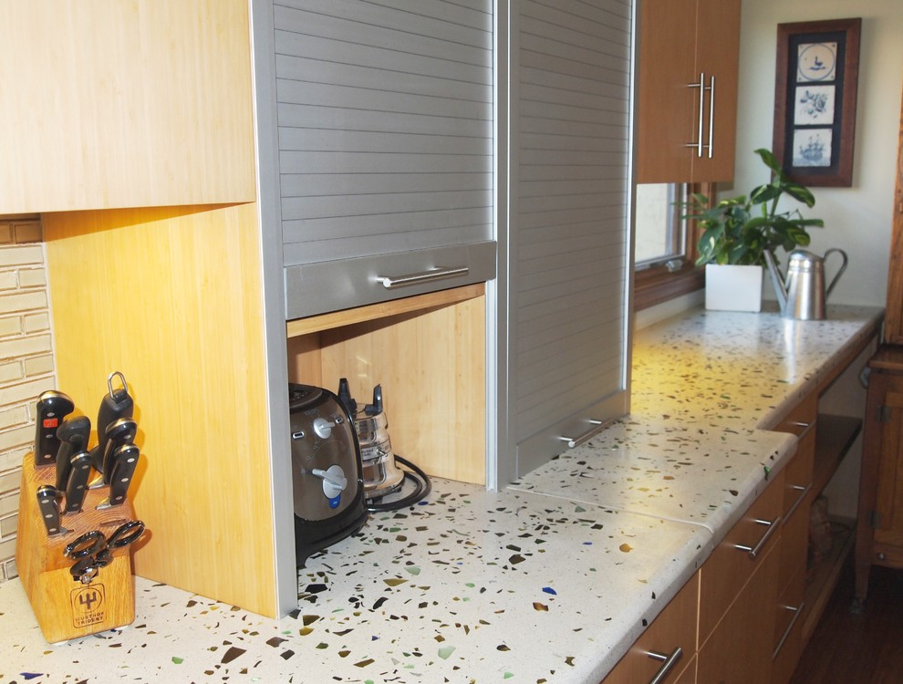 Inspiration for a large modern single-wall eat-in kitchen remodel in San Diego with flat-panel cabinets, light wood cabinets, recycled glass countertops, glass tile backsplash, an island, beige backsplash and stainless steel appliances