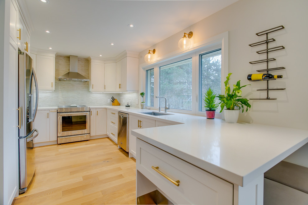 Mid-sized transitional medium tone wood floor eat-in kitchen photo in Toronto with an undermount sink, shaker cabinets, white cabinets, quartz countertops, multicolored backsplash, porcelain backsplash, stainless steel appliances, a peninsula and white countertops