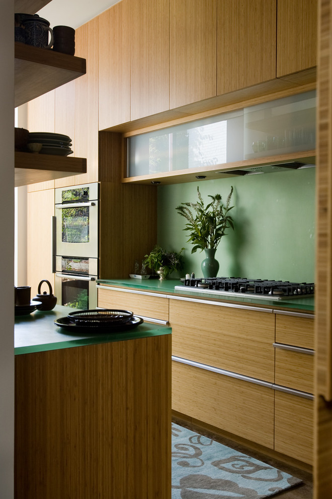 Trendy galley kitchen photo in Birmingham with flat-panel cabinets, light wood cabinets and stainless steel appliances