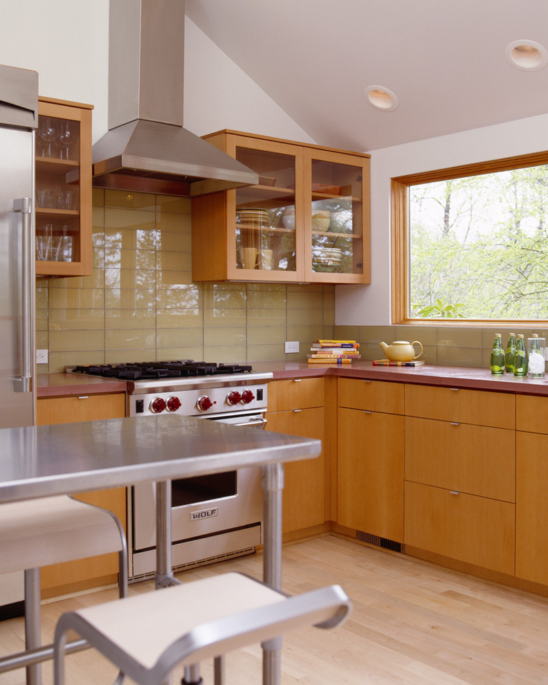 Minimalist l-shaped kitchen photo in Portland with glass-front cabinets, medium tone wood cabinets, concrete countertops, yellow backsplash, glass tile backsplash and stainless steel appliances