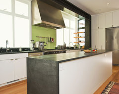 Kitchen with island and back-painted glass and exposed painted moment frame modern kitchen