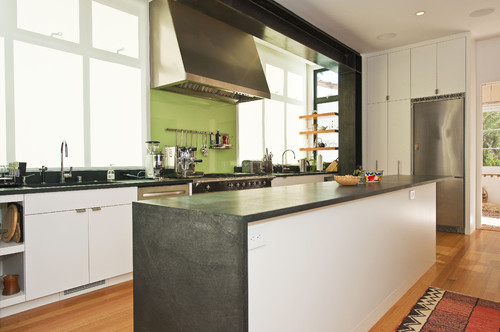 Kitchen with island and back-painted glass and exposed painted moment frame