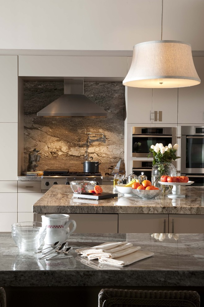 Eat-in kitchen - huge traditional eat-in kitchen idea in Orlando with stainless steel appliances, flat-panel cabinets, white cabinets, granite countertops, brown backsplash, an island and marble backsplash