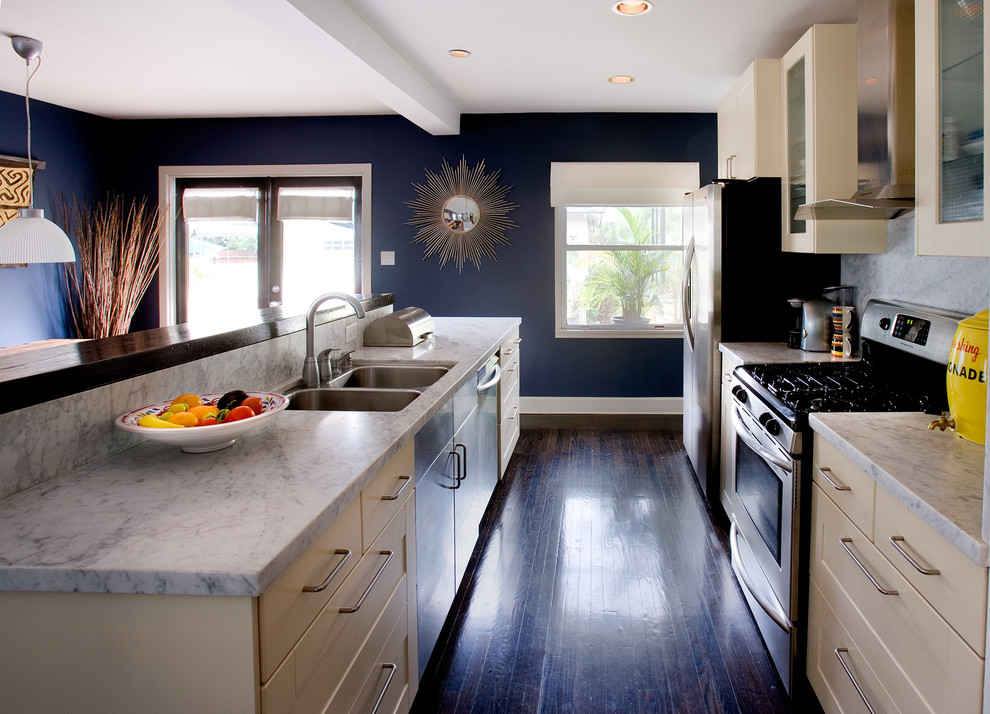 Trendy brown floor kitchen photo in Los Angeles with a double-bowl sink and marble backsplash