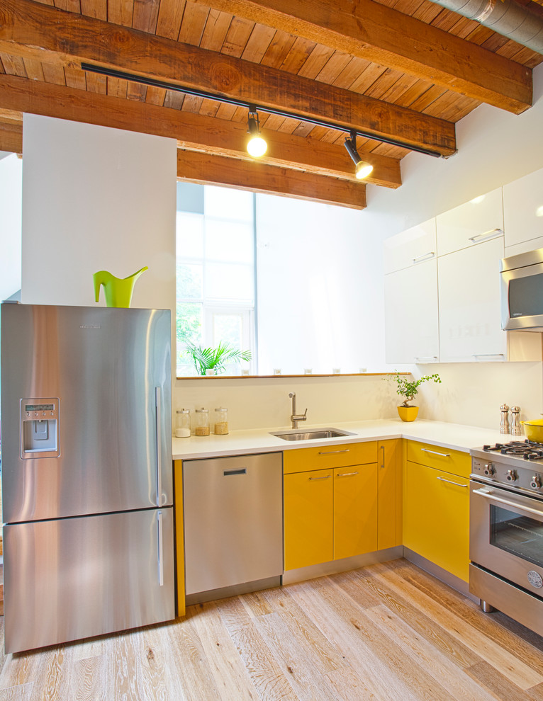 Example of a mountain style l-shaped kitchen design in Vancouver with stainless steel appliances, a single-bowl sink, flat-panel cabinets and yellow cabinets