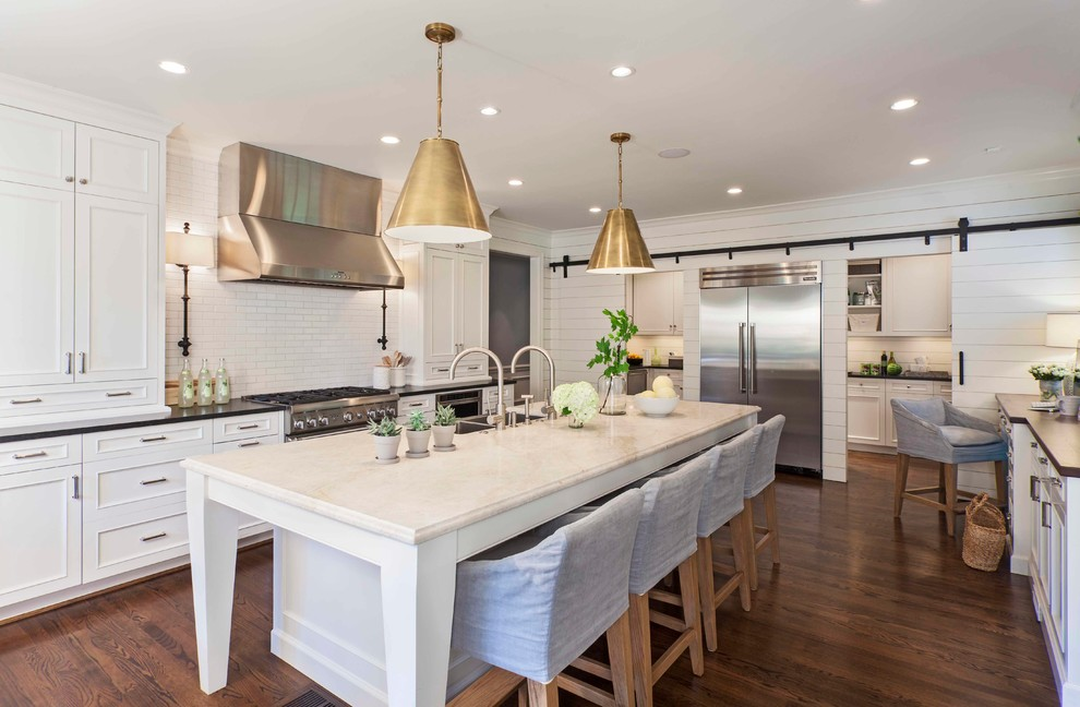 Transitional dark wood floor kitchen photo in Charlotte with a double-bowl sink, recessed-panel cabinets, white cabinets, solid surface countertops, white backsplash, subway tile backsplash, stainless steel appliances and an island