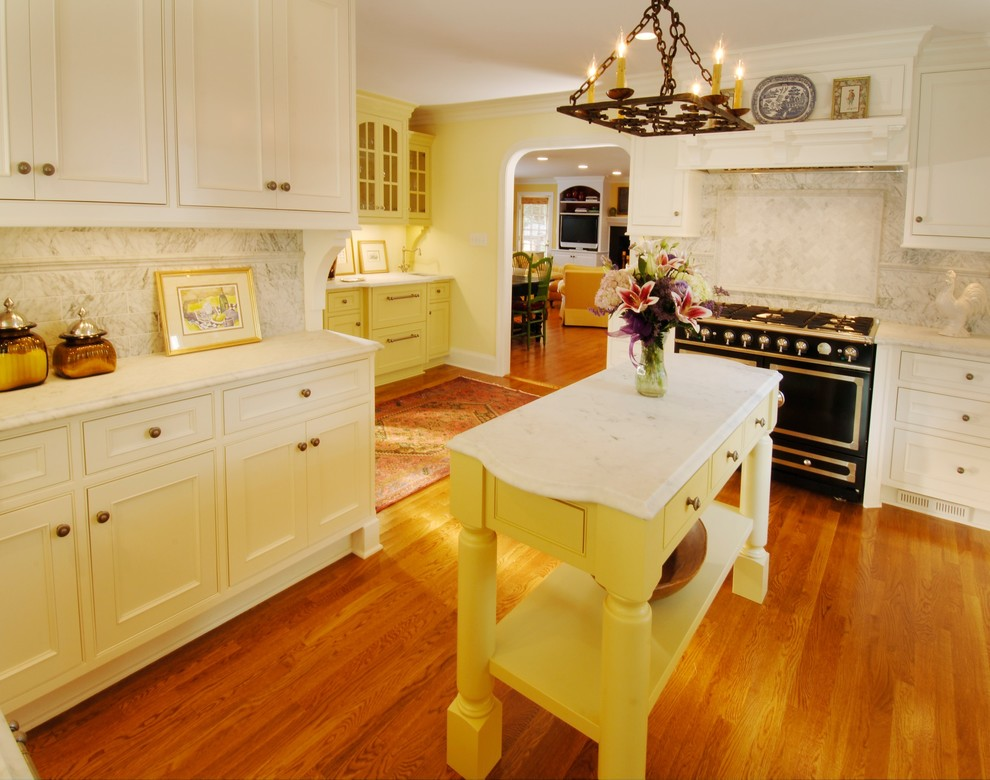 Kitchen - transitional kitchen idea in Charlotte with beaded inset cabinets, white cabinets, white backsplash and black appliances