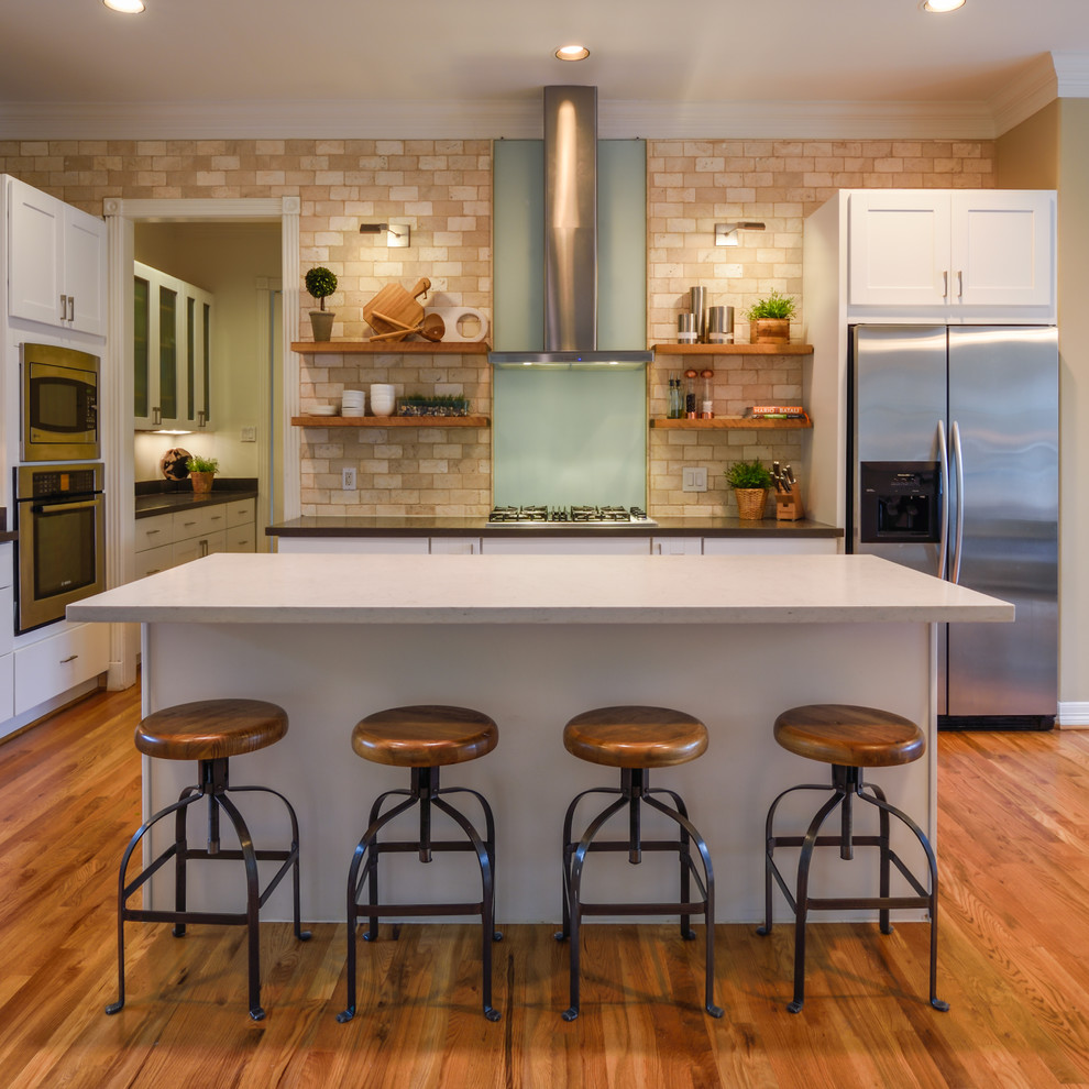 Large trendy l-shaped medium tone wood floor eat-in kitchen photo in Houston with shaker cabinets, white cabinets, beige backsplash, subway tile backsplash, stainless steel appliances and an island