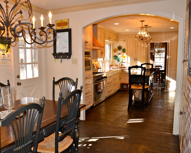 Eat-in kitchen - large traditional u-shaped dark wood floor and brown floor eat-in kitchen idea in Austin with a farmhouse sink, raised-panel cabinets, beige cabinets, granite countertops, white backsplash, stone tile backsplash, stainless steel appliances and an island