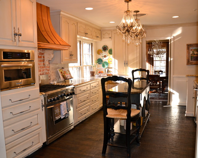 Large elegant u-shaped dark wood floor and brown floor eat-in kitchen photo in Austin with a farmhouse sink, raised-panel cabinets, beige cabinets, granite countertops, white backsplash, stone tile backsplash, stainless steel appliances and an island