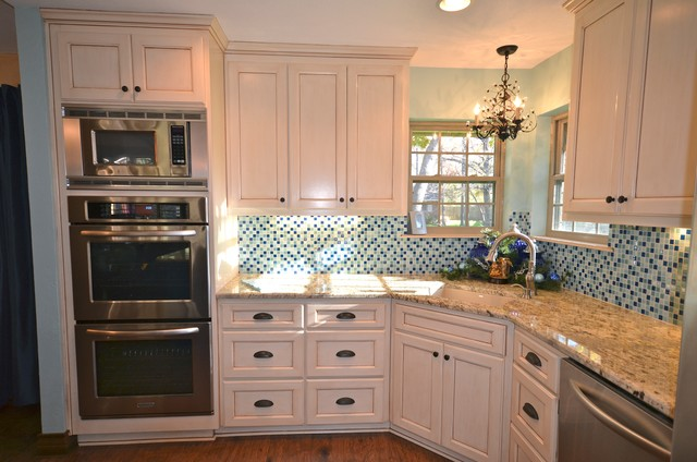 Inspiration for a mid-sized timeless medium tone wood floor and brown floor kitchen remodel in Austin with an undermount sink, recessed-panel cabinets, white cabinets, granite countertops, blue backsplash, glass tile backsplash and stainless steel appliances