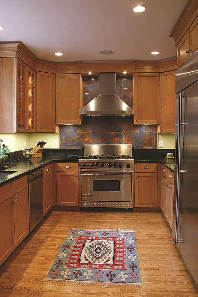 Example of a mid-sized trendy u-shaped medium tone wood floor and brown floor kitchen design in DC Metro with a double-bowl sink, no island, recessed-panel cabinets, brown cabinets, onyx countertops, multicolored backsplash, ceramic backsplash and stainless steel appliances
