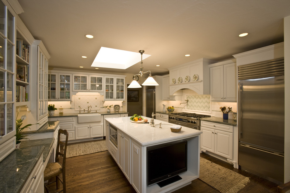 Inspiration for a timeless l-shaped enclosed kitchen remodel in San Francisco with glass-front cabinets, stainless steel appliances, a farmhouse sink, white cabinets and multicolored backsplash