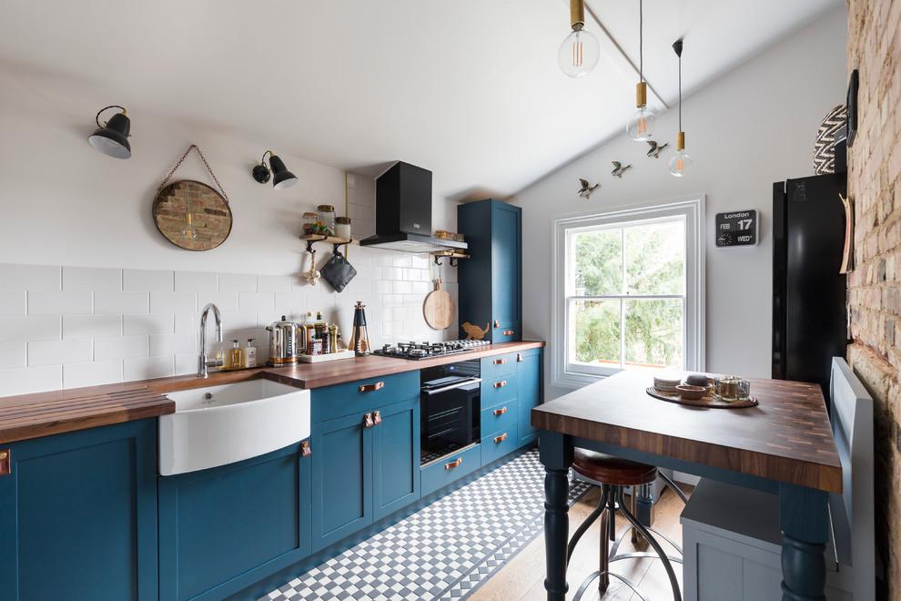 Idéer för vintage linjära kök, med en rustik diskho, skåp i shakerstil, blå skåp, vitt stänkskydd och svarta vitvaror